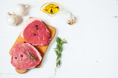 Raw meat with olive oil, spices and rosemary on white wooden board. Fresh beef. Ready to roasting Royalty Free Stock Photos