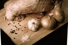 Raw meat, onion, garlic and spices on a wooden board. Toned.  Stock Photography