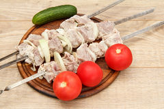 Raw meat and onions on skewers are ready for cooking. Fresh cucumber and tomatoes, meat chop slices on wooden chopping board Royalty Free Stock Images