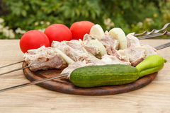 Raw meat and onions on skewers are ready for cooking. Fresh cucumber and tomatoes, meat chop slices on wooden chopping board Royalty Free Stock Photography