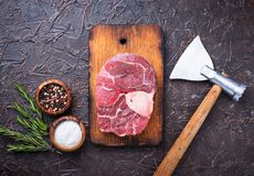 Raw meat osso buco and butchers axe. Top view Royalty Free Stock Photo