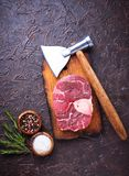 Raw meat osso buco and butchers axe. Top view Stock Image