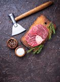 Raw meat osso buco and butchers axe. Top view Stock Photo