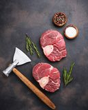 Raw meat osso buco and butchers axe. Top view Stock Photography