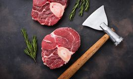 Raw meat osso buco and butchers axe. Top view Stock Photos