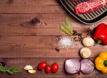 Raw meat in a pan on brown boards. Nearby spices, condiments an stock image