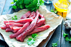 Raw meat. On paper and on a table Royalty Free Stock Photos