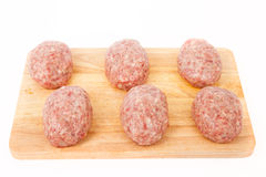 Raw meat patties on a wooden board on a white background Royalty Free Stock Images