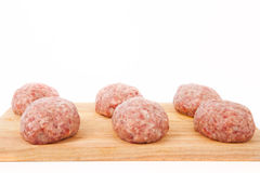 Raw meat patties on a wooden board on a white background Royalty Free Stock Photos