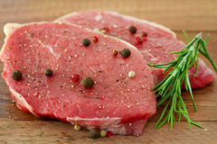 Raw meat with pepper. And rosemary Stock Photos