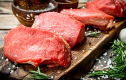 Raw meat. Pieces of fresh beef with spices and herbs royalty free stock photography