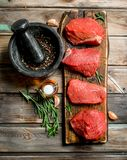 Raw meat. Pieces of fresh beef with spices and herbs stock photo
