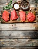Raw meat. Pieces of fresh beef with spices and herbs stock photos