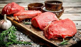 Raw meat. Pieces of fresh beef with spices and herbs stock photography