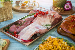 Raw meat pieces and ice. Small tomatoes and herb. Fresh pork for steaks. Table in the restaurant kitchen Stock Images