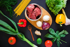 Raw meat in a plate on board, pasta and fresh vegetables on dark background. Top view. Flat lay. Food background. Raw meat in a plate on board, pasta and fresh Royalty Free Stock Photo