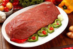 Raw meat on the plate with vegetables.  Royalty Free Stock Photo