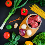 Raw meat in plate on wooden board and fresh vegetables on dark background. Top view. Flat lay. Food background. Raw meat in plate on wooden board and fresh Stock Images