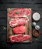 Raw meat. Pork and beef steaks on a tray with spices and rosemary sprig stock photo