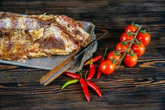 Raw meat. Raw pork meat on a cutting board vegetables and spices on black background. Stock Images