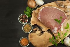 Raw meat pork steak on a cutting board. Preparing barbecue pork steak. Sales of pork on the grill. Advertising on butcher. Royalty Free Stock Image
