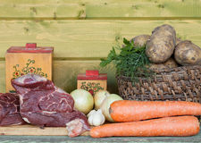 Raw meat, potato, onion, garlic, carrot and dill on wooden table.  Royalty Free Stock Photos