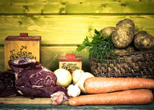 Raw meat, potato, onion, garlic, carrot and dill on wooden table. Toned Royalty Free Stock Image