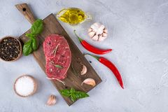 Raw meat. Raw beef steak on a cutting board with greens and spices. On a gray concrete background Royalty Free Stock Photography
