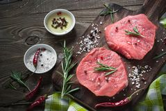 Raw beef steak on a cutting board. Raw meat. Raw beef steak on a cutting board with herbs and spices. Top view with copy space Royalty Free Stock Photography