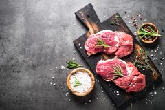 Raw beef steak with herbs. Raw meat. Raw beef steak on a cutting board with rosemary and spiceson dark stone table. Top view with copy space Royalty Free Stock Photo