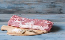 Raw meat. Raw pork steak on black with salt and spices. Stock Photography
