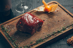 Raw meat Ribeye Steak. Raw fresh meat Ribeye Steak, seasoning and meat fork on dark background Stock Image