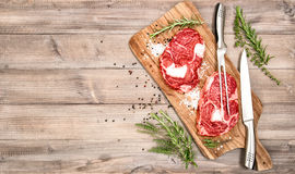 Raw meat. Ribeye Steak with herbs and spices. On wooden kitchen desk. Food background Stock Photos