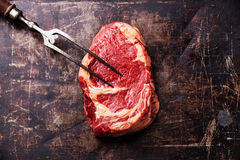 Raw meat Ribeye Steak and meat fork Royalty Free Stock Images