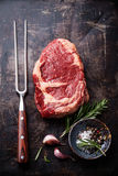 Raw meat Ribeye Steak, meat fork and seasonings Stock Image