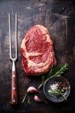 Raw meat Ribeye Steak, meat fork and seasonings. Raw fresh meat Ribeye Steak, meat fork and seasonings on dark metal background Stock Image