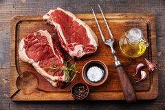 Raw meat Ribeye Steak, seasoning and meat fork
