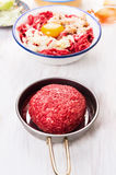 Raw meat rissoles in frying pan Royalty Free Stock Image