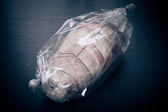 Raw meat with rope in the package on a black background. Toned.  Stock Image
