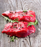 Raw meat with rosemary. And spices on wooden table Royalty Free Stock Images