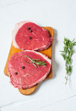 Raw meat and rosemary on white wooden board. Fresh beef. Ready to roasting. Stock Photos