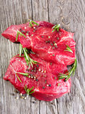 Raw meat with rosemary. On wooden table Stock Photos