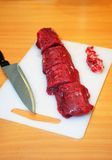 Raw meat selection on wooden cutting board with knife Royalty Free Stock Photography