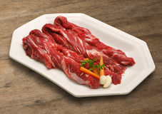 Raw meat selection on wooden cutting board. Royalty Free Stock Image