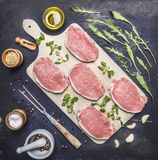Raw Meat set Pork steaks with herbs and spices on a white cutting board wooden rustic background top view. Raw Meat set Pork steaks with herbs and spices on a Stock Photos