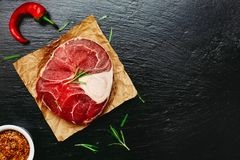 Raw meat shank. With chili peppers and rosemary leaves on a dark stone surface. Top view. Flat lay. Copy space Stock Images