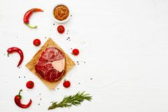 Raw meat shank with chili peppers and rosemary on a white painte. D wooden surface. Top view. Flat lay. Copy space Royalty Free Stock Image