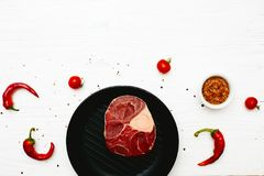 Raw meat shank with chili peppers and tomatoes on a white painte. D wooden surface. Top view. Flat lay. Copy space Royalty Free Stock Photo