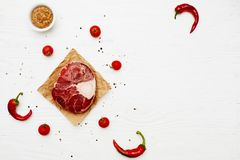 Raw meat shank with chili peppers and tomatoes on a white painte. D wooden surface. Top view. Flat lay. Copy space Royalty Free Stock Photography