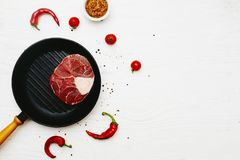 Raw meat shank  with  dijon mustard, chili peppers and tomatoes. In a grill frying pan on a white painted wooden surface. Top view. Flat lay. Copy space Stock Photography